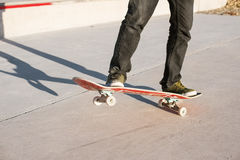 A young guy on a skateboard in a manual on a skatepark on the background of house Stock Photos