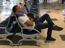 A young guy is sleeping on a chair at the airport, putting a pillow under his head,. A young man is sleeping on a chair at the airport, putting a pillow under royalty free stock photo
