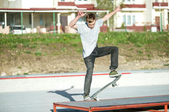 A young guy slides on a skateboard in a manual on a skatepark on the background of house Royalty Free Stock Image