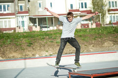 A young guy slides on a skateboard in a manual on a skatepark on the background of house Stock Image