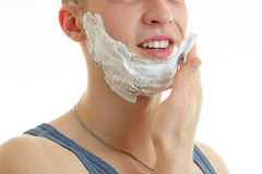 Young guy smiles and deals the hand shaving foam on beard close-up Stock Photo