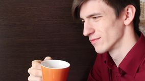 A young guy smiles, takes a slow sip from an orange mug stock video footage