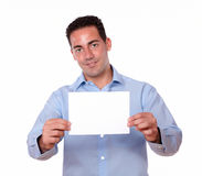 Young guy smiling and holding white card Royalty Free Stock Photo
