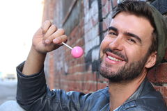 Young guy smiling surrounded by graffiti walls holding a pink lollipop Royalty Free Stock Photo