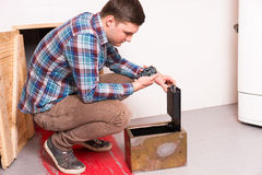 Young guy squatting and opened the safe looks at the puzzle tryi. Ng to get out of the kitchen with a bloody floor, escape the room game concept Stock Image