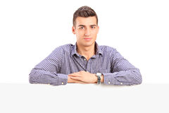Young guy standing behind a blank panel Royalty Free Stock Image
