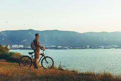 Young Guy Standing With Bike On Coast And Enjoying View of Nature Sunset Vacation Traveling Relaxation Resting Concept. A young hipster guy cyclist with a Royalty Free Stock Image