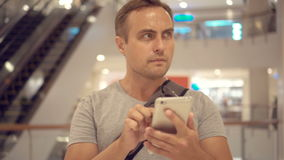 Young guy standing in shopping mall using smartphone, browsing, reading news, chatting with friends stock video footage