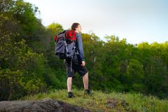 Young guy standing on top of the mountain, enjoying the view. Be. Autiful forest background Royalty Free Stock Photos