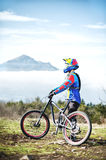 A young guy standing on your mountain bike atop a mountain, when below the mountains low clouds Royalty Free Stock Image