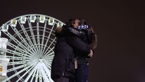Young guy meets with his girlfriend near ferris wheel. Young guy stands at the blurred ferris wheel background and waits someone. Suddenly young girl runs to stock video footage