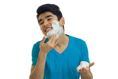 Young guy strikes shaving foam on your face and laughs Stock Photo