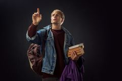 Young guy, a student. With books and a backpack reaching somewhere hand. Place for your design stock photography