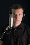 Young guy with the studio microphone. On dark background Royalty Free Stock Image