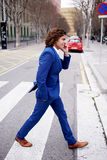 Young guy in a stylish blue suit talking on the phone going over the road Royalty Free Stock Photos