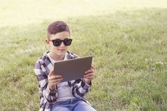 Young guy with stylish haircut using tablet pc stock photo