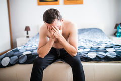 Young guy suffering from headache in bed at home royalty free stock photography