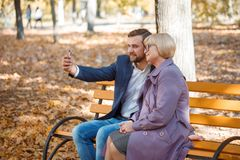 A guy doing selfie with his mother on a bench in an autumn park. A young guy in a suit does selfie with his mother in a purple coat on a bench in an autumn park Stock Images