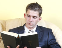 Young guy in a suit reads the Bible Royalty Free Stock Images