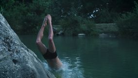 A young guy on a summer holiday or vacation jumping from a stone in the middle of a mountain forest lake. Jumps into the