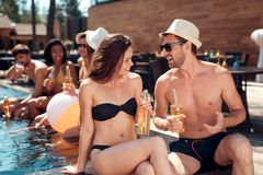 Young guy in summer straw hat flirts with girl in swimsuit sitting in pool. Swimming pool party. Company of friends are having fun in swimming pool Royalty Free Stock Photography