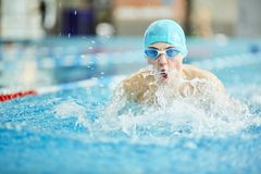 Swim competition. Young guy in swimwear swimming in water during sports competition Stock Photography