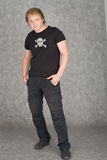 Young guy in a T-shirt with piracy symbolics. The young guy in a T-shirt with piracy symbolics on gray Stock Photo