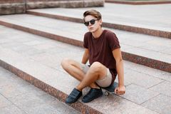 Young guy in a T-shirt with sunglasses and shorts sitting. On a skateboard Royalty Free Stock Photos