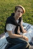 Young guy with tablet sitting in the park on the rug green grass royalty free stock photos