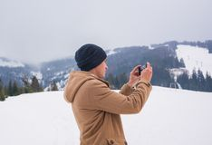 A young guy takes a picture of a mountain landscape on a cellpho Stock Images