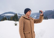 A young guy takes a picture of a mountain landscape on a cellpho Royalty Free Stock Image