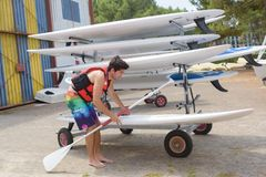 Young guy taking paddle board from stack at sailing club. Paddle royalty free stock image