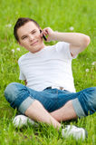 Young guy talking on mobile phone. Portrait of a happy young guy talking on mobile phone in a park - Outdoor Stock Photography