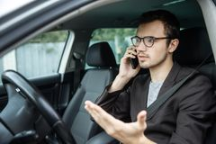 Young guy talking on the phone while sitting at his car. Road safety concept royalty free stock image
