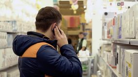 Young guy is talking on the phone, standing in electrical goods department, chandeliers, in the building materials store. Young guy is talking on the phone stock video footage