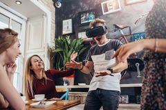 Young guy testing virtual reality headset screaming playing scary game while his cheerful pretty female friends laughing royalty free stock photo