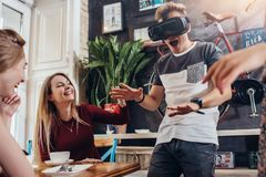 Young guy testing virtual reality headset screaming playing scary game while his cheerful pretty female friends laughing royalty free stock images