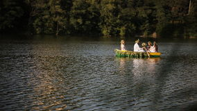 Young guy and three girls swimming in the boat stock footage