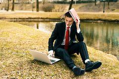 Young guy tired of work. man in a suit running on the nature near the lake. royalty free stock images