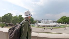 A young smiling man, tourist standing with a backpack, in a hat and admires the Magic Montjuic. Of Montjuc near the National Palace, where the National Museum stock footage