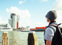 Young guy tourist looking to view Rotterdam city harbour, future. Architecture concept, industrial lifestyle real modern people concept stock photos
