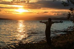 A young guy tourist spread his arms wide and enjoys a beautiful sunset over the lake. A midges fly around him, which glows in the royalty free stock photo