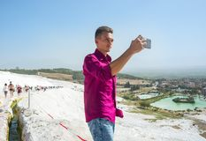 Young guy, tourist, takes pictures with his mobile phone view Pa Royalty Free Stock Photography