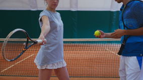 Young guy training the girl on the tennis court stock footage