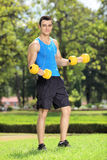 Young guy training with two dumbbells in a park Royalty Free Stock Photo