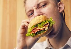 Guy is really trying to burger. The young guy is really trying to burger and looking at camera Stock Images