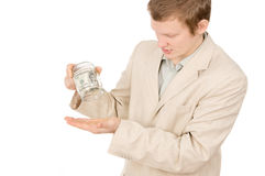 A young guy trying to extract money from a glass container Royalty Free Stock Image