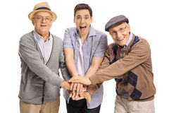 Young guy and two mature men putting their hands together. And looking at the camera isolated on white background stock photography