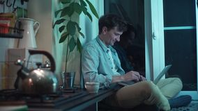 Young guy using computer sitting at kitchen while kettle boiling on stove stock footage