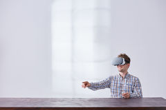 Young guy using innovative glasses. Young guy having fun while using innovative glasses in white living room royalty free stock photos